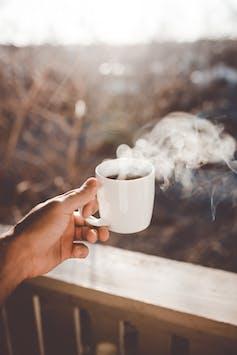 Hand holding steaming coffee mug