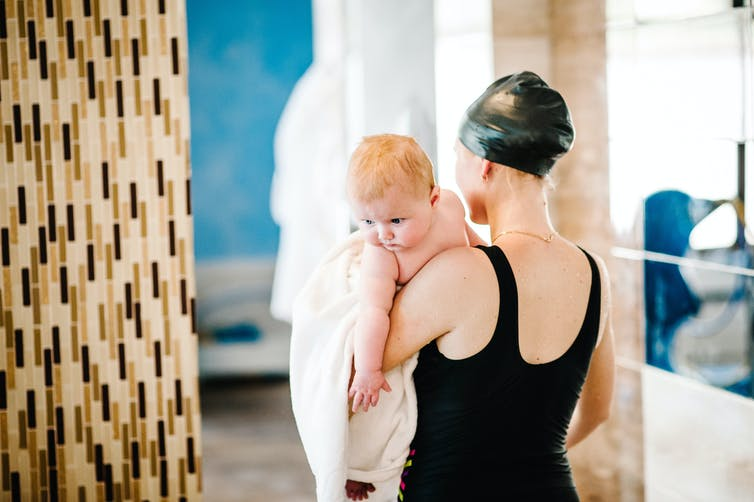 A woman holds a baby in a pool change room.