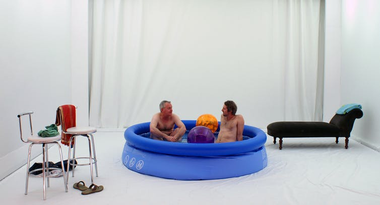 A stage. Two men in a wading pool.