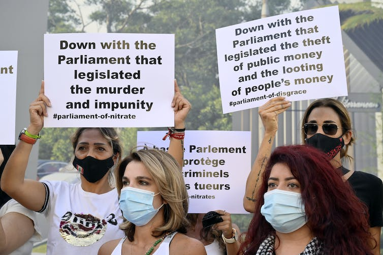 Protesters wearing COVID masks hold anti-government banners during a march in Beirut in September 2021.