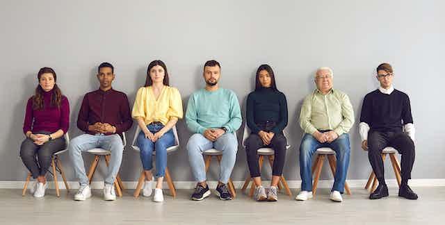 Un groupe d'hommes et de femmes assis, attendant à l'hôpital.