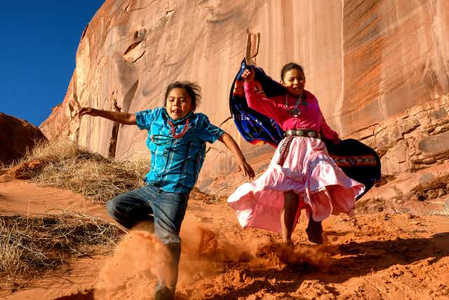 Two Native American children dressed in traditional clothing run in a desert canyon.