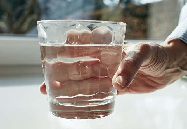 A woman holds out a glass of water with a wind in the background