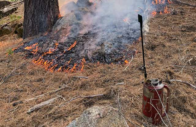 A small fire and a drip torch used by firefighters to set controlled burns.