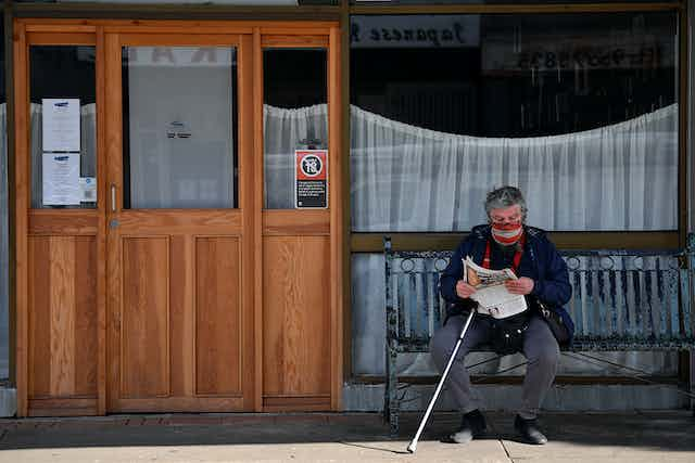 Older man in a mask and with a walking stick sits on a bench, reading the paper.