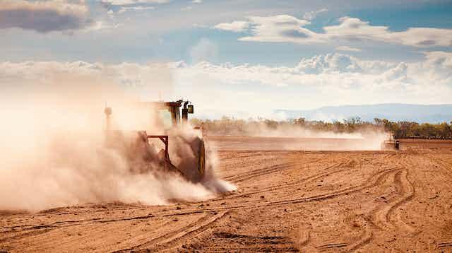 tractor ploughs dusty field