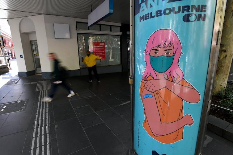 Billboard przedstawiający kobietę rysunkową z różowymi włosami i bandażem po zaszczepieniu.