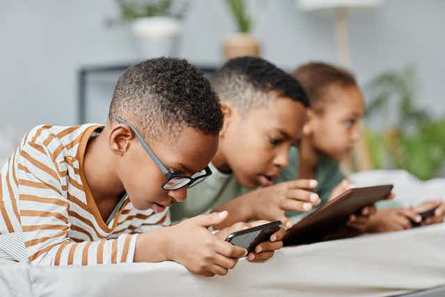 Three children on electronic devices