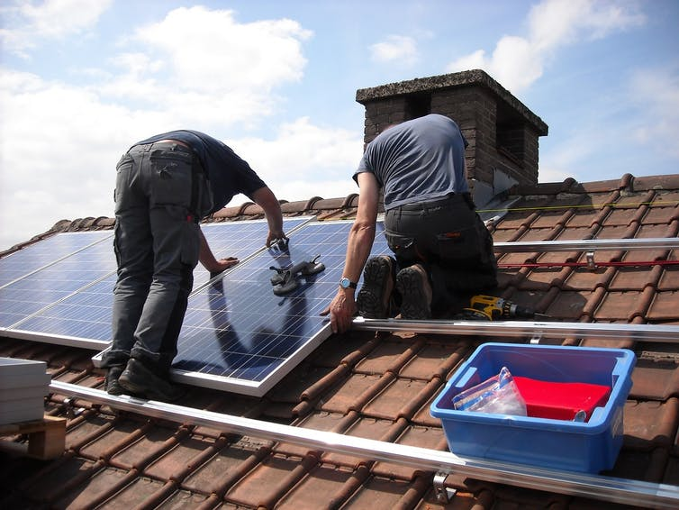 Two people work on a solar panel on a roof