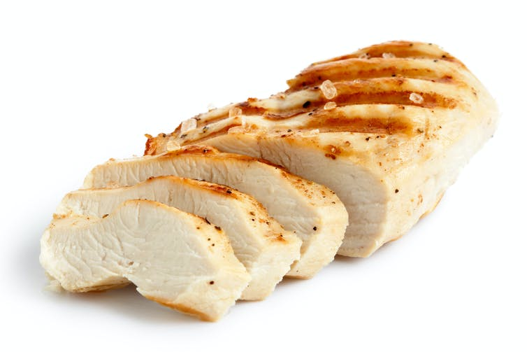 A partially sliced grilled chicken breast.