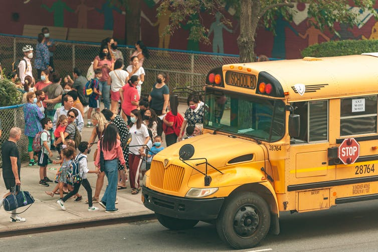 School children line up to get on a yellow schoolbus in New York City