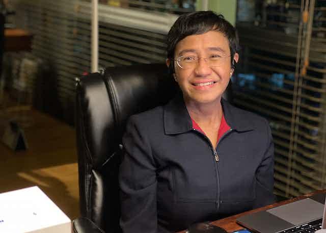 Maria Ressa sat at a desk, smiling