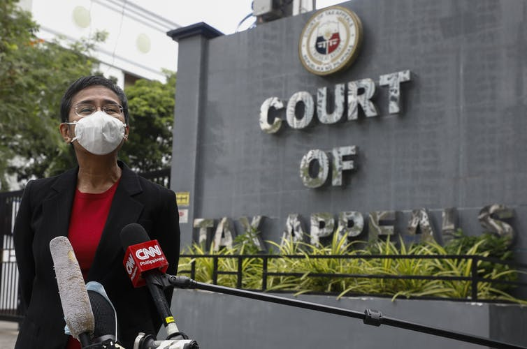 Maria Ressa wearing a face mask, speaking into microphones, next to Court of Tax Appeals sign.