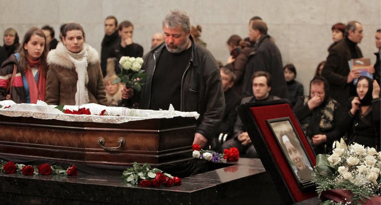 Dmitry Muratov brings flowers to an open coffin with crowd behind