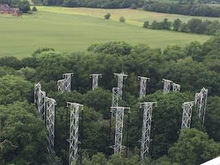 Una vista aérea de un trozo de bosque rodeado por torres de metal.