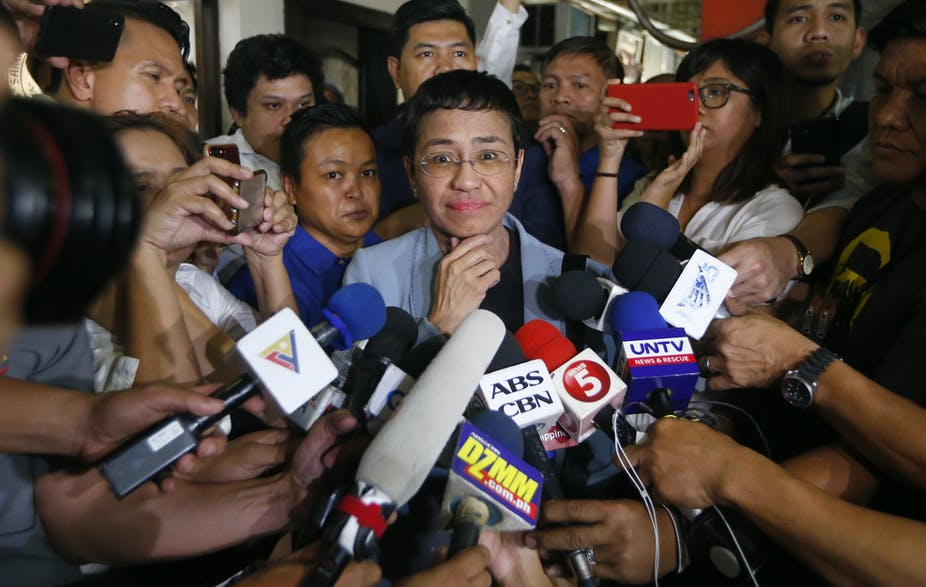 Maria Ressa smiles at the camera while surrounded by TV news reporters and microphones.