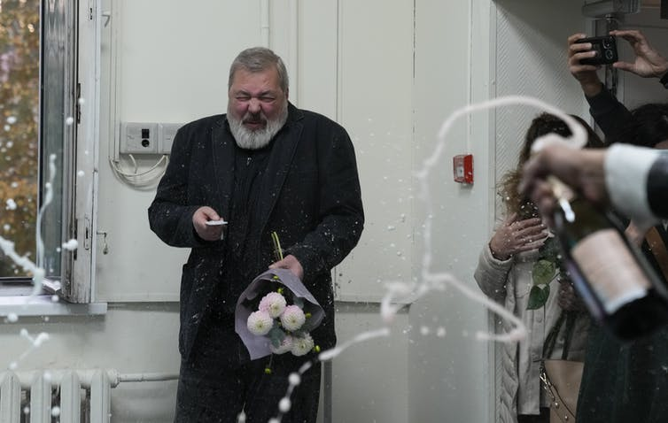 Dmitry Muratov cowers from streams of champagne fly out of bottles held by well-wishers.