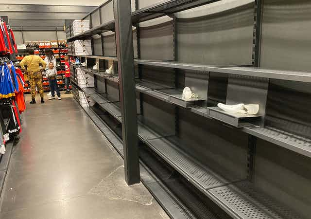 Empty shelve that would have normally been filled with shoes sit empty as customers of a Nike outlet store look at stuff that's actually in stock at the end of the aisle