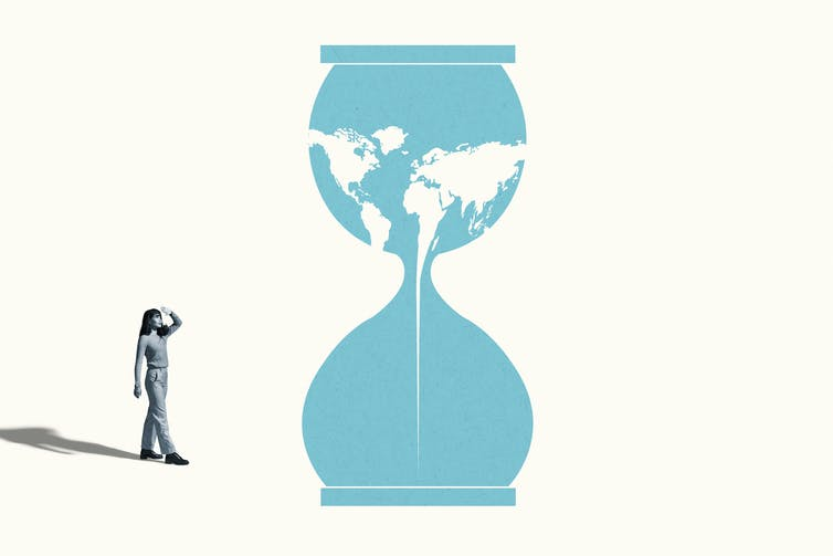 Woman looks at hourglass with map of world dripping through the opening.