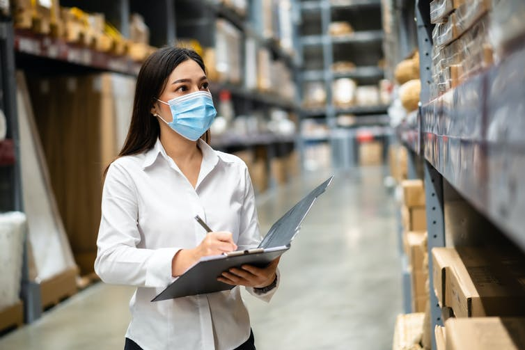 Masked woman with a clipboard surveys a storeroom.