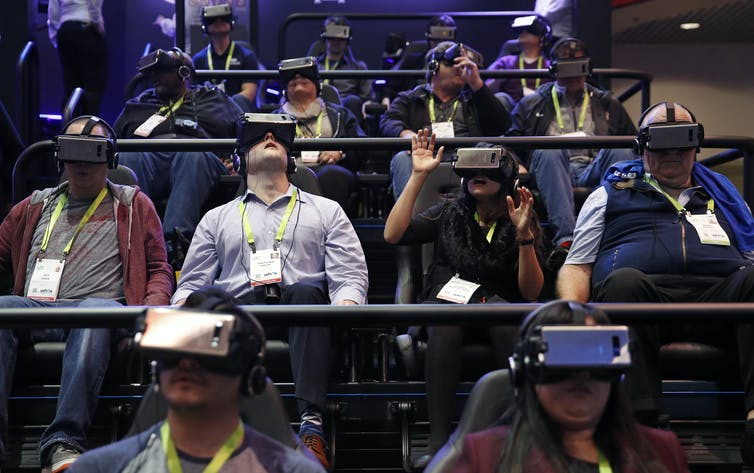 An audience wearing virtual reality headsets.
