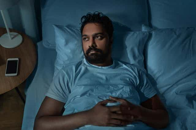 A man looks worried while lying in bed.