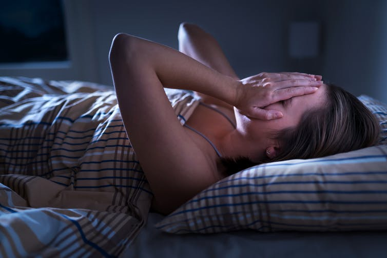 A woman covers her face while lying awake in bed.