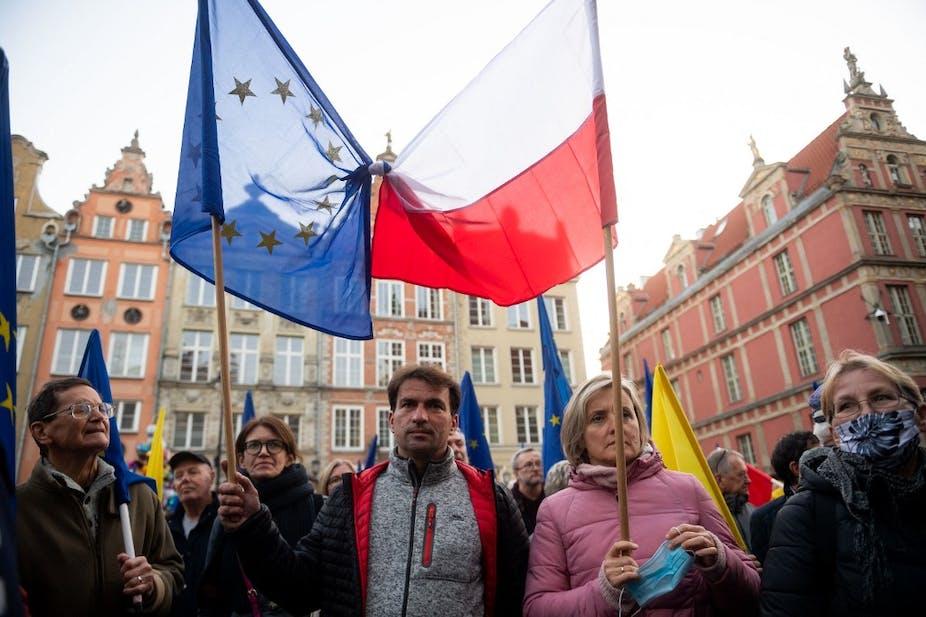 Drapeaux polonais et européens noués ensemble pendant une manifestation en ville.