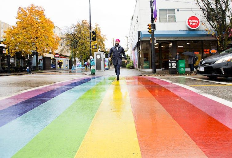 NDP leader Jagmeet Singh crosses the road at a rainbow crosswalk.