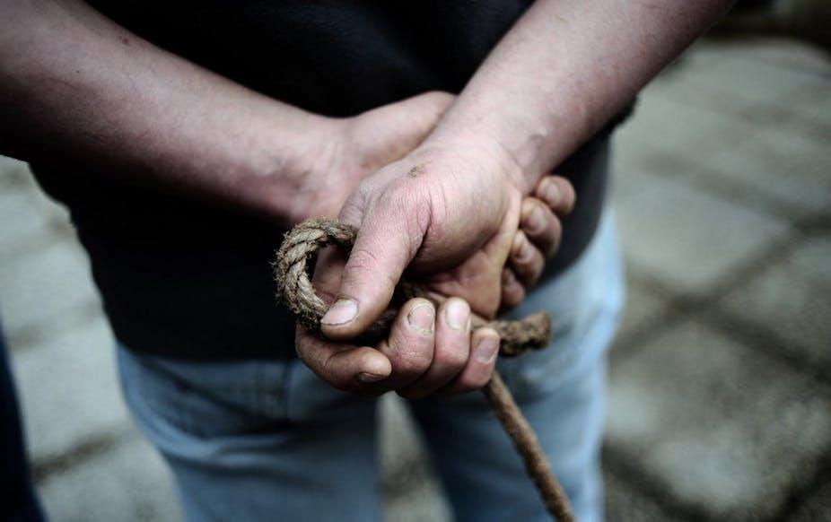Deux mains d'un éleveur vues de dos.