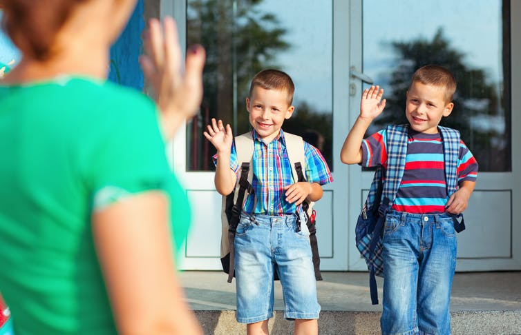 Two young boys wave to mother at school entrance