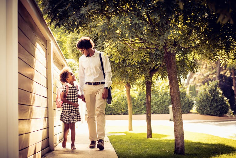 Father and daughter laugh together as they walk to school.