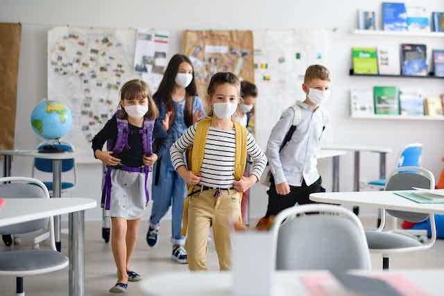 Children wearing masks enter classroom