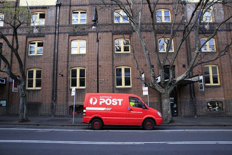 An Australia Post van waits outside a building.