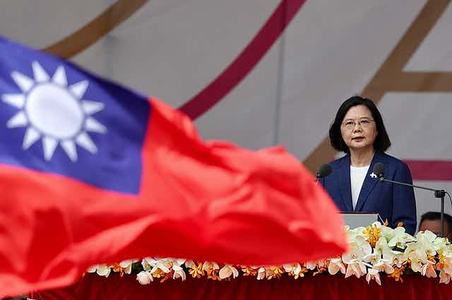 Taiwanese president, Tsai Ing-wen, delivers a speech with a Taiwanese national flag waving in the foreground.ei, Taiwan, 10 October 2021.