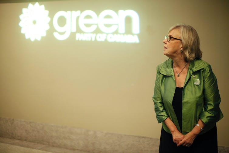 May is standing in front of the Green Party symbol wearing a green jacket.