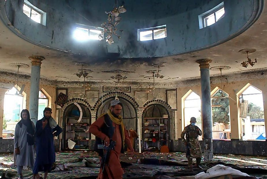 Taliban fighters investigate inside a Shiite mosque after a suicide bomb attack in Kunduz on October 8, 2021.