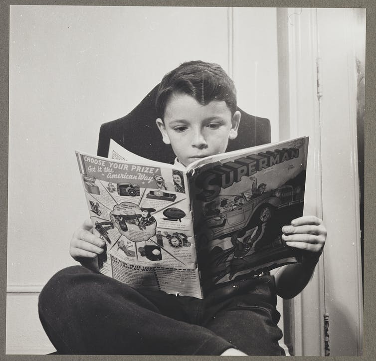Vintage photo of a boy reading Superman