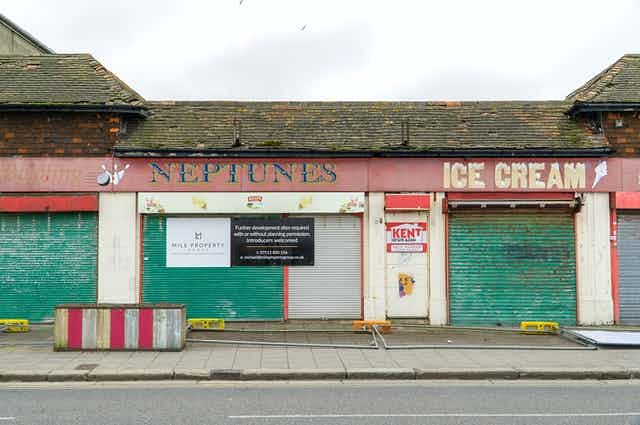 A row of dingy boarded-up shops painted red with green shutters.