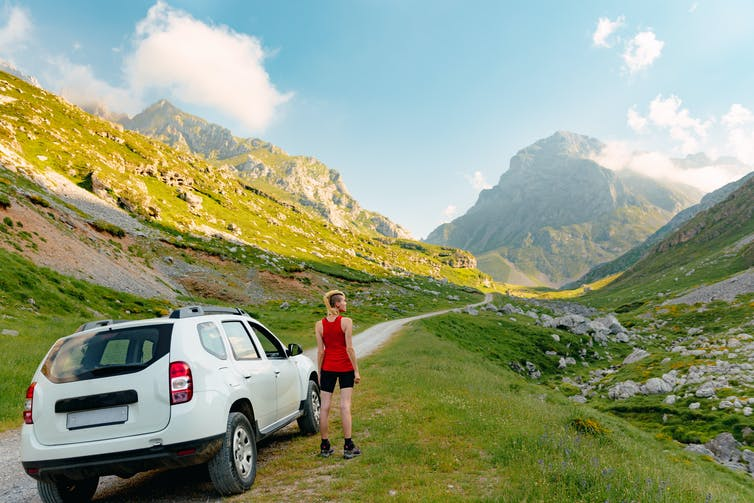 Woman Standing Beside Her Suv Looking At The Mountains