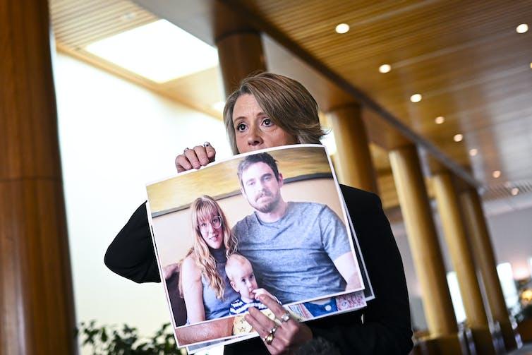Labor senator Kristina Keneally holds up photos of Australians stranded.