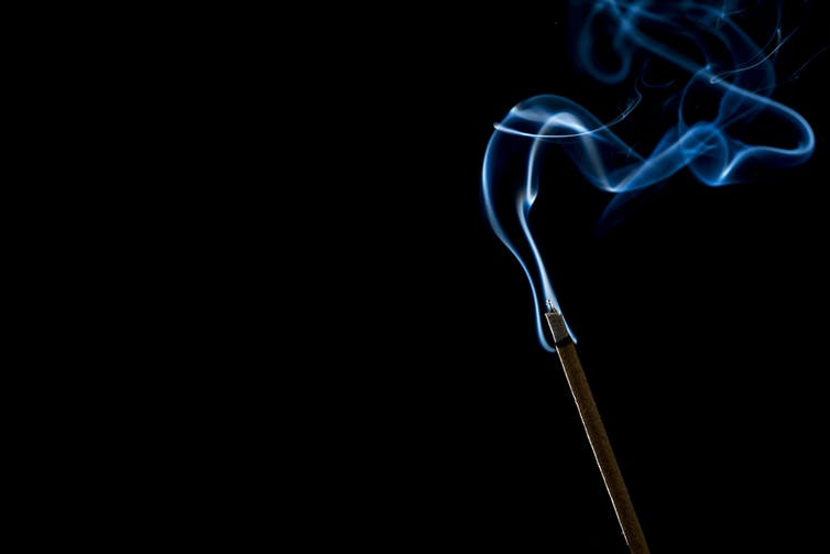 Lit incense stick with smoke wafting