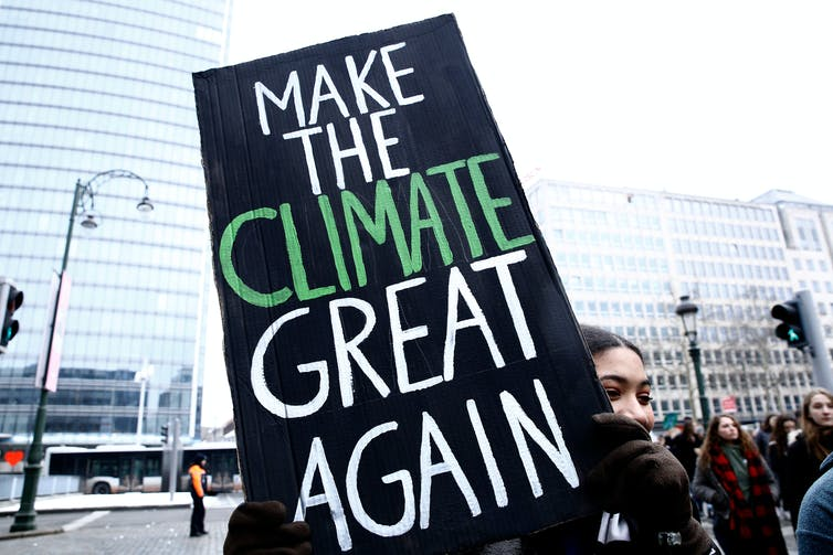 Woman holds sign reading 'Make the Climate Great Again'
