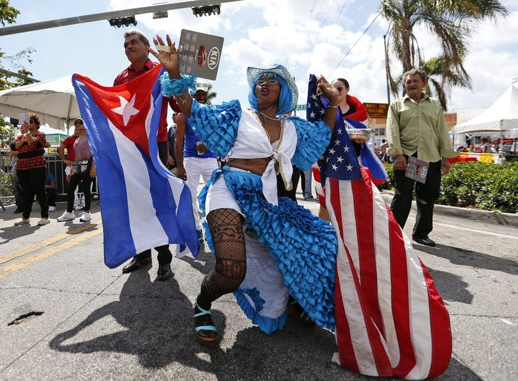 People celebrate in a festival and wave Cuban and American flags.