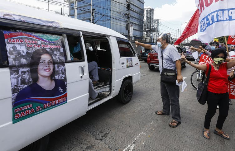 Protesters shake their fists at a minibus with a photograph of Sarah Duterte, who is believed to be preparing a bid for the Philippine presidency.