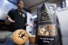 Oatmeal s'mores cannabis edibles, packaged and unpackaged, in the foreground, with a man out of focus in the background