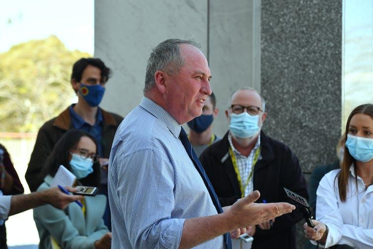 man in blue shirt talks to journalists