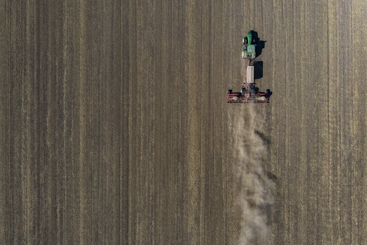 A green tractor pulls a seed drill behind it in a plowed field.