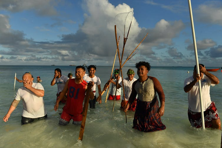 people stand in water with spears