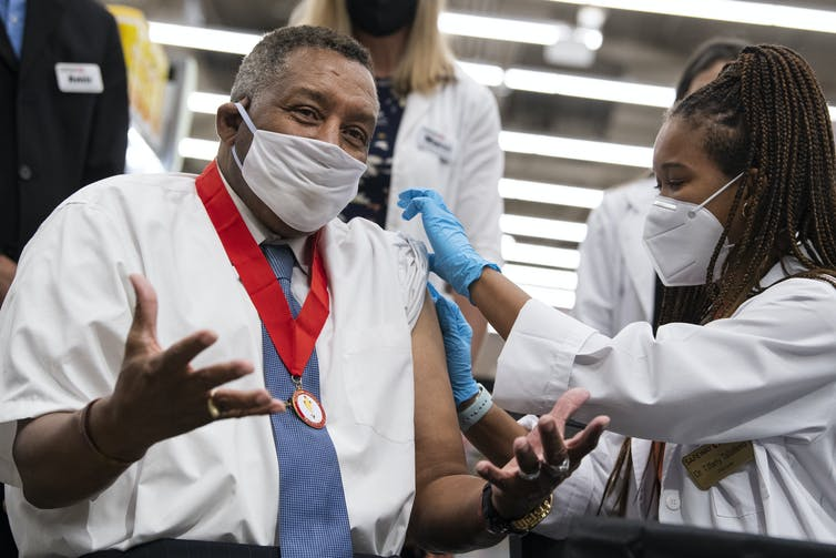 A man wearing a mask receives a COVID-19 vaccine booster.